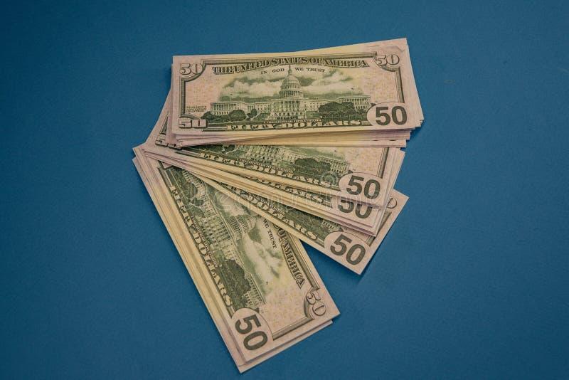 Wielka Gruba pieniądze rolka Odizolowywająca na błękitnym tle obraz royalty free