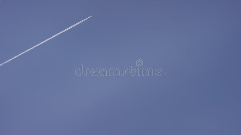 Wielka pasażerska naddźwiękowego samolotu latająca wysokość w jasnym niebieskim niebie, opuszcza długiego białego ślad Samolotowy obraz royalty free