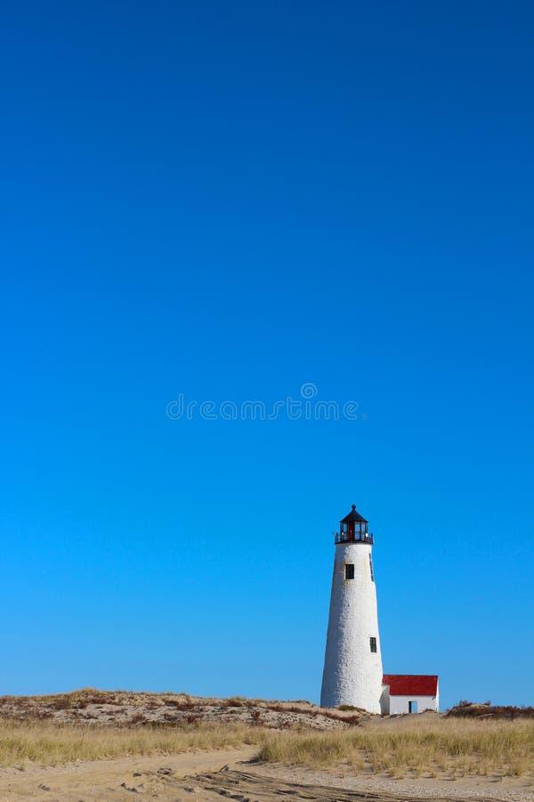 Wielka punktu światła latarnia morska Nantucket z niebieskim niebem, Plażową trawą i diunami, zdjęcie royalty free