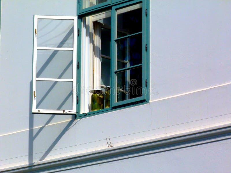 Wielka szklana zalewa zgrzyta w okno z zielonymi pickes wśrodku poniższego jaskrawego słońca z zielonymi nadokiennymi ramami fotografia stock
