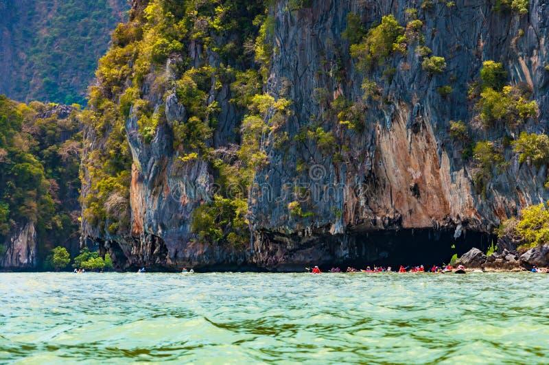 Wielka wapień skała z jamy i turysty kajakarstwem w Phang nga obraz royalty free