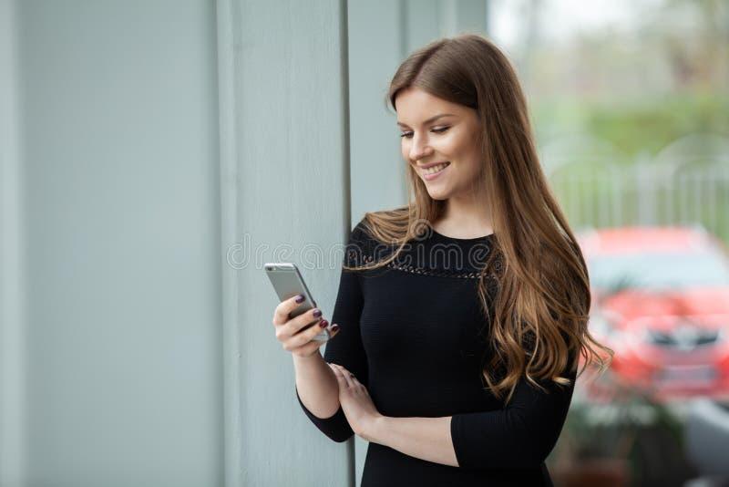 Wielka wiadomość! Rozochocona młoda piękna kobieta używa jej smartphone z uśmiechem przy jej biurem podczas gdy stojący zdjęcia royalty free