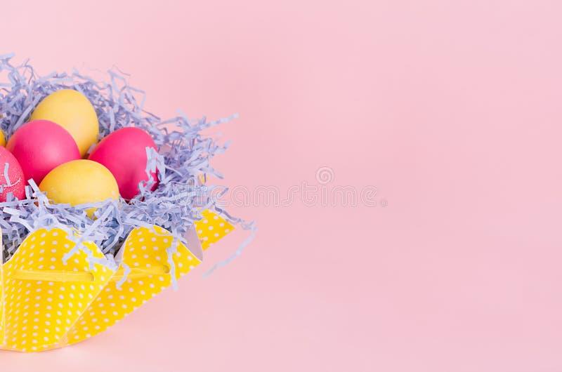 Wielkanoc domowy wystrój różowy tło, kopii przestrzeń - domowej roboty malujący jajka w pastelowym żółtym koszu na świetle - zdjęcie royalty free