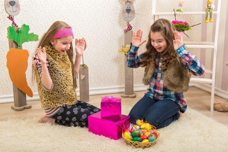 Wielkanoc - Dwa siostry, dziewczyna zaskakiwali Wielkanocnego prezent obrazy stock