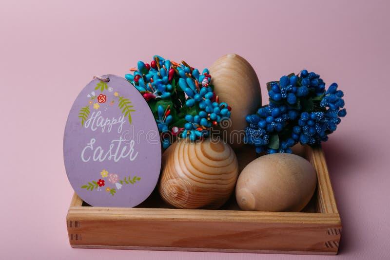 Wielkanoc, jajka od drewna, pysanka, zbierać, kwiaty i inskrypcja na karcianej szczęśliwej wielkanocy, fotografia stock