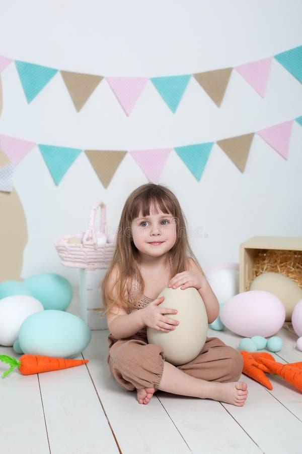 Wielkanoc! Mała dziewczynka w kombinezonach siedzi z wielkim Wielkanocnym jajkiem Wielkanocna lokacja, dekoracje Rodzinni wakacje fotografia stock
