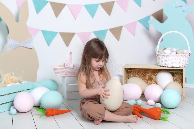 Wielkanoc! Mała dziewczynka w kombinezonach siedzi z wielkim Wielkanocnym jajkiem Wielkanocna lokacja, dekoracje Rodzinni wakacje zdjęcie royalty free