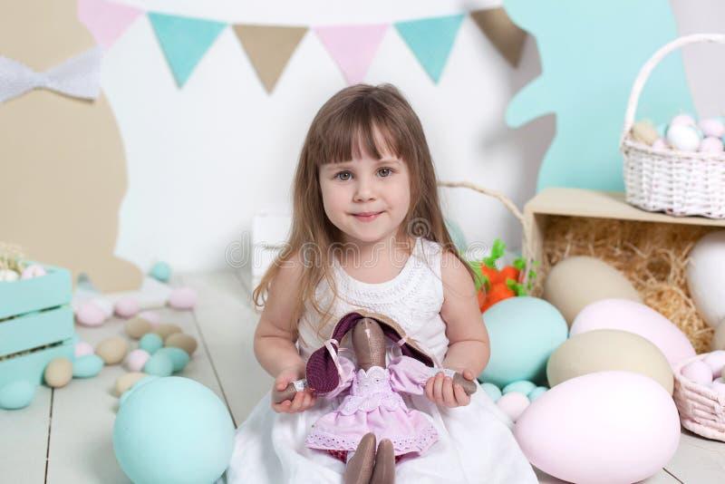 Wielkanoc! Piękna mała dziewczynka w białej sukni ściska Wielkanocnego królika Wiele różni kolorowi Wielkanocni jajka, kolorowy i zdjęcie stock