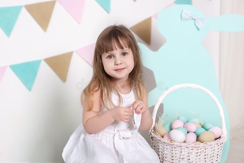 Wielkanoc! Piękna mała dziewczynka w białej sukni z Wielkanocnymi jajkami i koszem na jaskrawej Wielkanocnej scenerii Wielkanocna obrazy stock