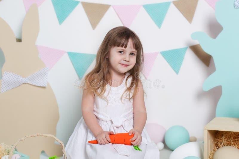 Wielkanoc! Piękna mała dziewczynka w biel sukni obsiadaniu z Wielkanocnymi królikami i marchewkami jajko kolorowy kr?lik Wiele r? obrazy stock