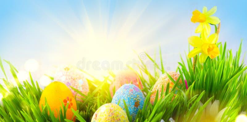 Wielkanoc Piękni kolorowi jajka w wiosny trawy łące nad niebieskim niebem z słońce granicy projektem zdjęcie stock