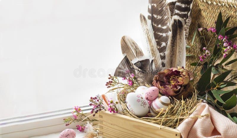 Wielkanoc tła szczęśliwy Różowi Wielkanocni jajka w gniazdeczku z kwiecistymi dekoracjami i piórkami blisko okno fotografia stock