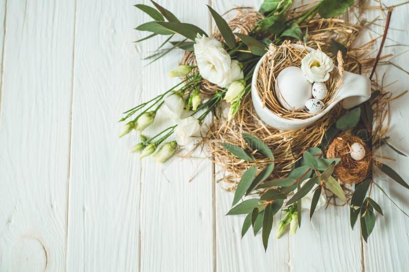 Wielkanoc tła szczęśliwy Wielkanocni jajka w filiżance na drewnianym białym tle z kwiecistą dekoracją pojęcie Easter szczęśliwy zdjęcie stock