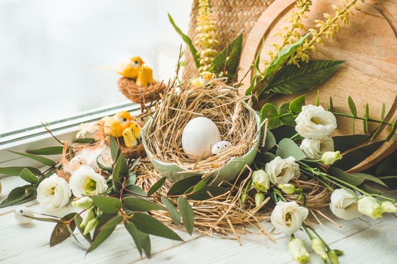 Wielkanoc tła szczęśliwy Wielkanocny jajko w gniazdeczku z kwiecistą dekoracją blisko okno jako wiele tło jajka przepiórka pojęci zdjęcie royalty free