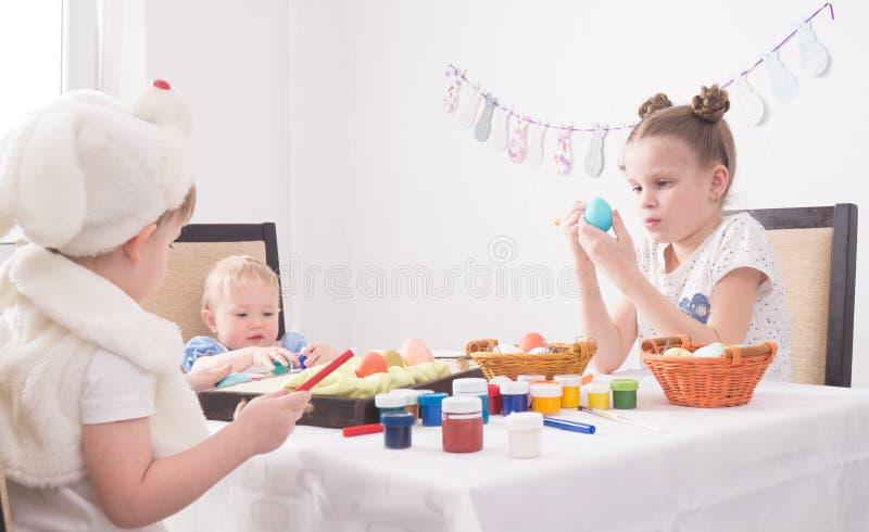 Wielkanoc w rodzinnym okręgu: Dzieci przy stołowej farby Wielkanocnymi jajkami obraz stock