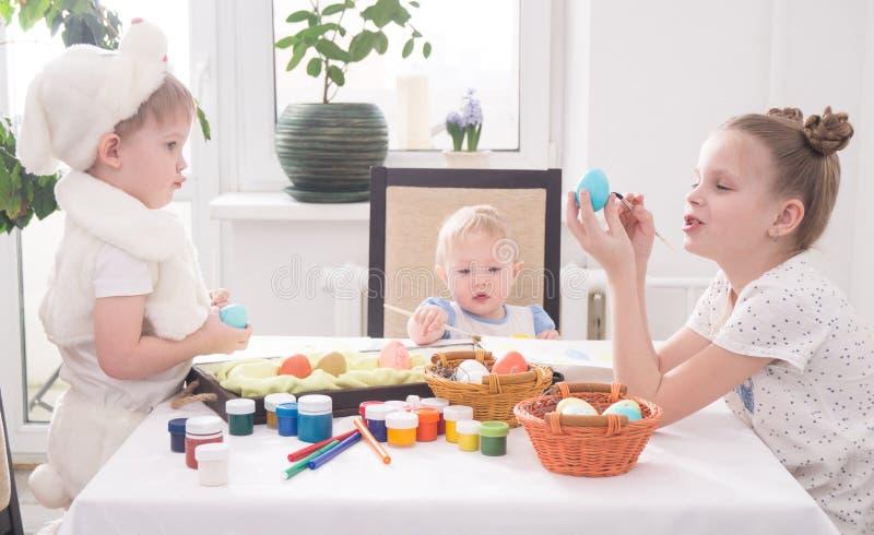 Wielkanoc w rodzinnym okręgu: Dzieci przy stołowej farby Wielkanocnymi jajkami obraz royalty free