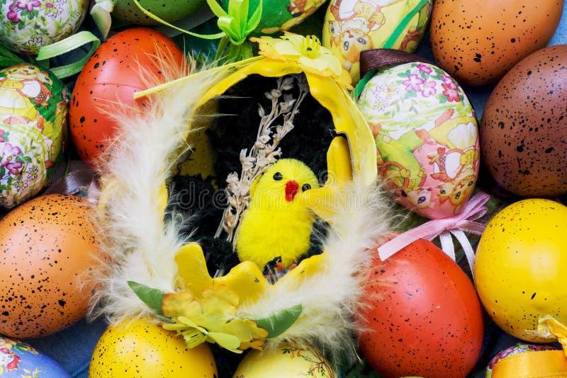Wielkanoce malujący jajka i żółty kurczątko zdjęcie royalty free