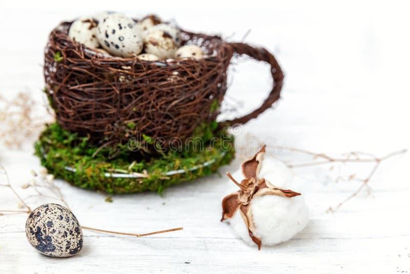 Wielkanocna dekoracja z jajkiem w gniazdowej filiżance i bawełna na bielu wykładamy marmurem tło obrazy stock