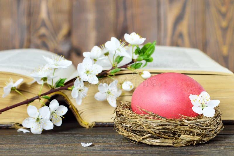 Wielkanocna karta z Wielkanocnym jajkiem w gniazdeczku, wiosna kwiatach i starej książce, fotografia royalty free