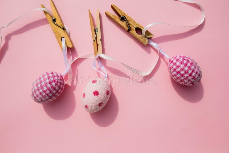 Wielkanocna scena z rzędem obwieszenia barwiący jajka i szpilka odizolowywający na różowym tle Szczęśliwy Easter skład dla wiosny zdjęcie stock