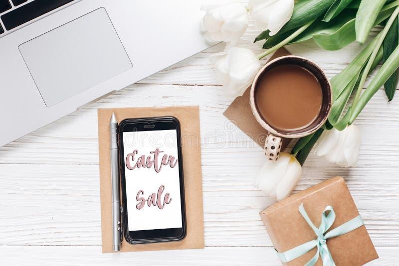 Wielkanocna sprzedaż na pustym telefonu ekranie, laptopie z ranek kawą i fotografia royalty free