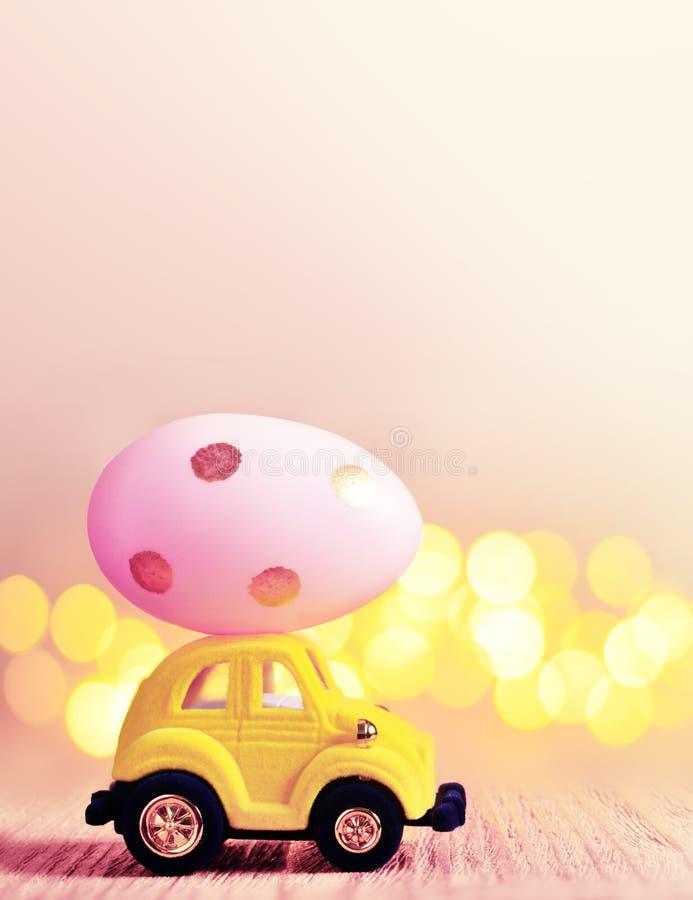 Wielkanocnego jajka i zabawki samochód na lekkim bokeh tle, szczęśliwy Easter dnia pojęcie zdjęcie royalty free