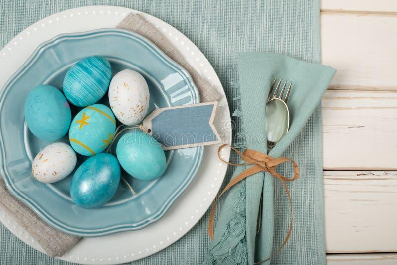 Wielkanocnego jajka miejsca Obiadowy położenie w Nautycznych kolorach Błękitnych cyraneczka Z biel z i talerzami, Silverware, suk fotografia stock