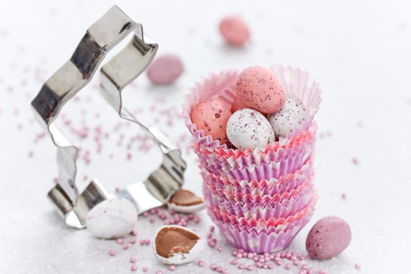 Wielkanocnego królika ciastka krajacz i czekoladowego cukierku mini jajka w pape fotografia stock