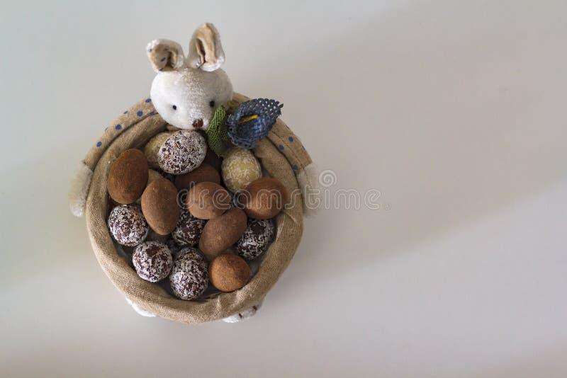 Wielkanocnego królika kosz z czekoladowymi jajkami na bielu stole obraz royalty free