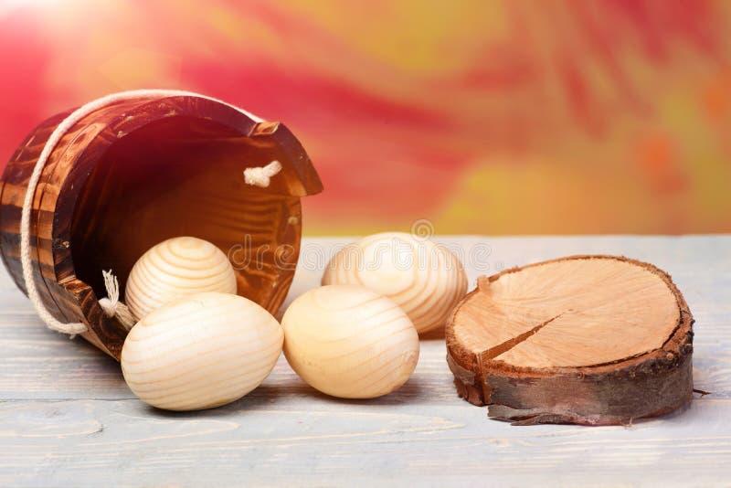 Wielkanocni beżowi drewniani jajka w drewnianym wiadrze blisko drzewnego fiszorka zdjęcia stock