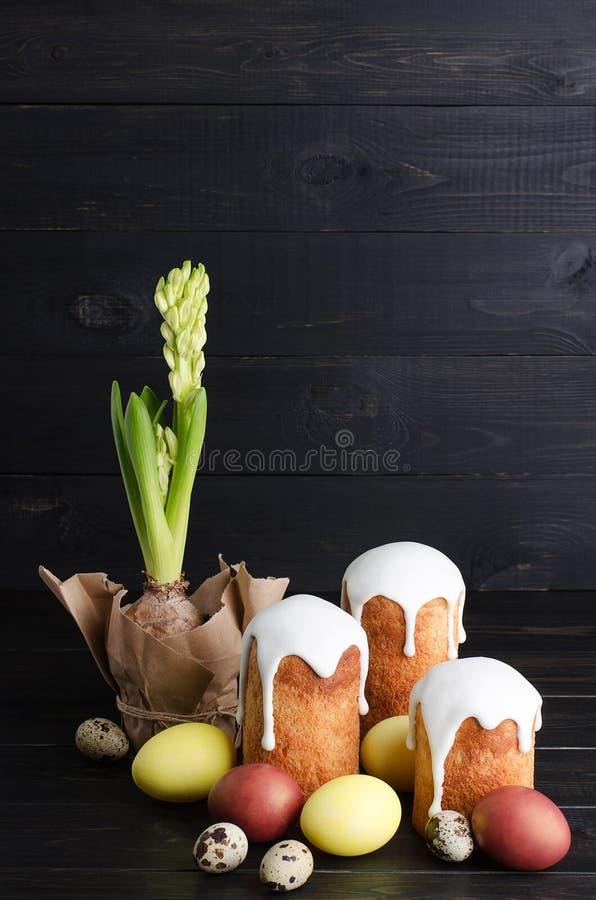 Wielkanocni jajka, Easter tort i hiacynty na ciemnym tle, zdjęcie stock