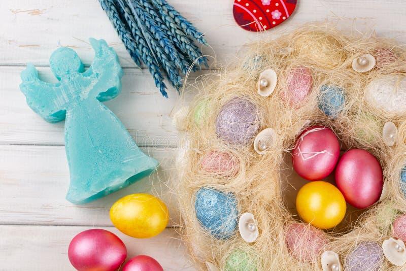 Wielkanocni jajka i anio? ?wieczka na nieociosanym drewnianym stole kolor t?a wakacje czerwonego ? zdjęcie stock