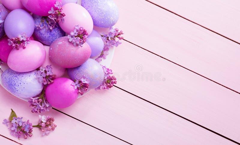 Wielkanocni jajka i kwiaty bez na różowym drewnianym stole Odgórny widok fotografia stock