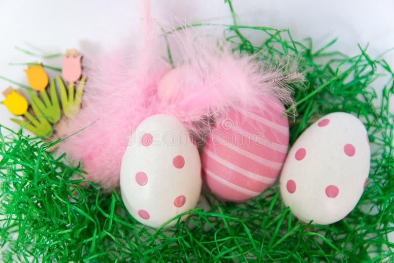 Wielkanocni jajka i piórka na zielonej trawie fotografia stock