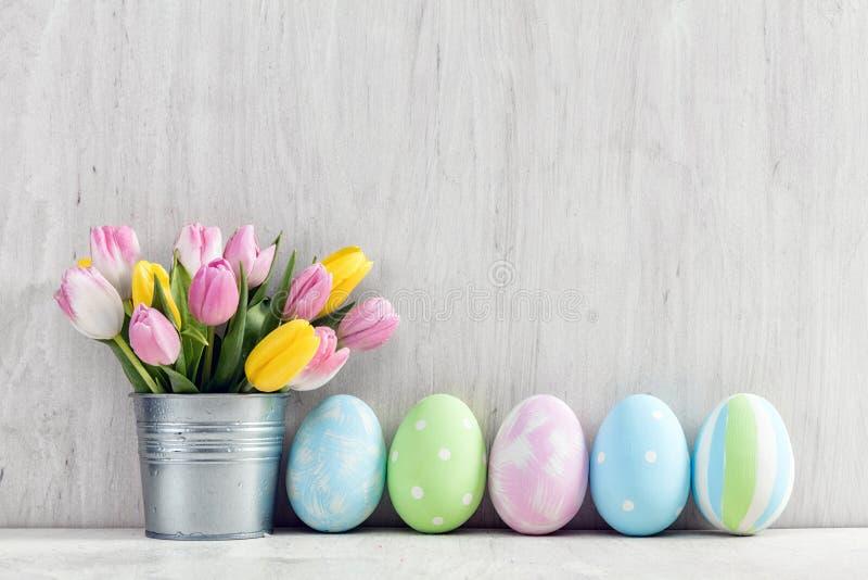 Wielkanocni jajka i wiosna bukiet tulipany na drewnianym stole fotografia stock