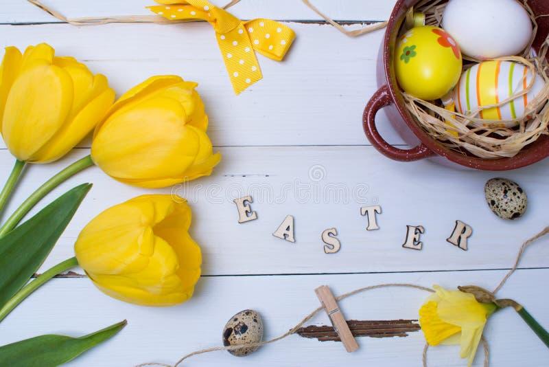 Wielkanocni jajka, tulipany i inne dekoracje nad białym drewnianym stołem, Odgórny widok zdjęcia royalty free