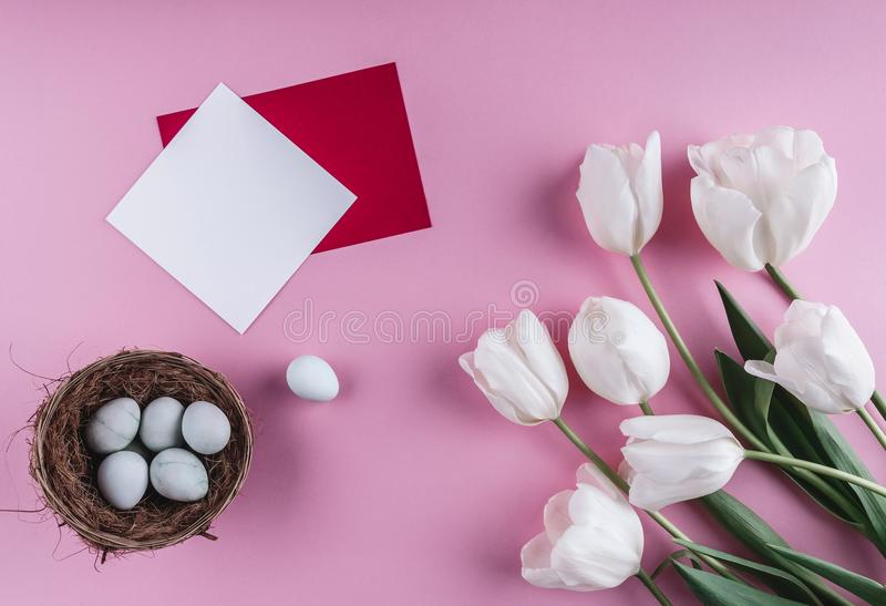 Wielkanocni jajka w gniazdeczka i tulipanu kwiatach na wiosny tle Odgórny widok z kopii przestrzenią Wielkanoc karty szczęśliwy obraz royalty free
