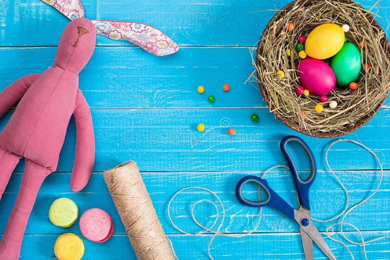 Wielkanocni jajka w gniazdeczku i króliku na błękitnych nieociosanych drewnianych deskach obrazy royalty free