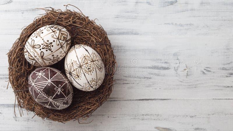 Wielkanocni jajka w gniazdeczku na drewnianym tle zdjęcia stock