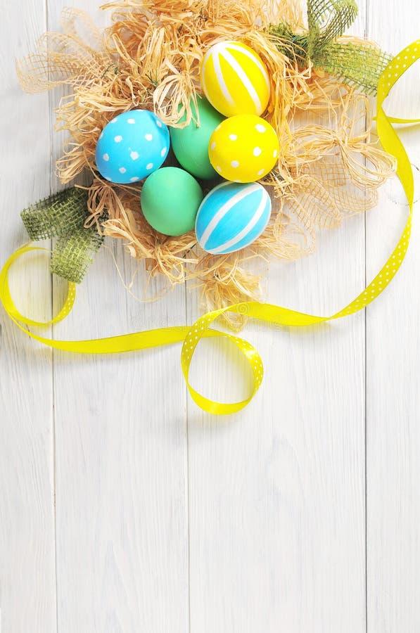 Wielkanocni jajka w gniazdeczku na nieociosanym białym tle obrazy stock