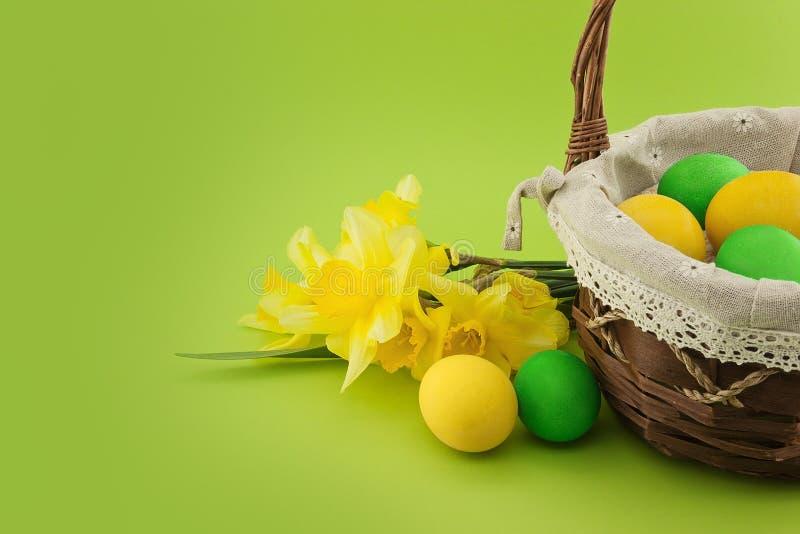 Wielkanocni jajka w koszu z bukietem żółty daffodil obraz royalty free
