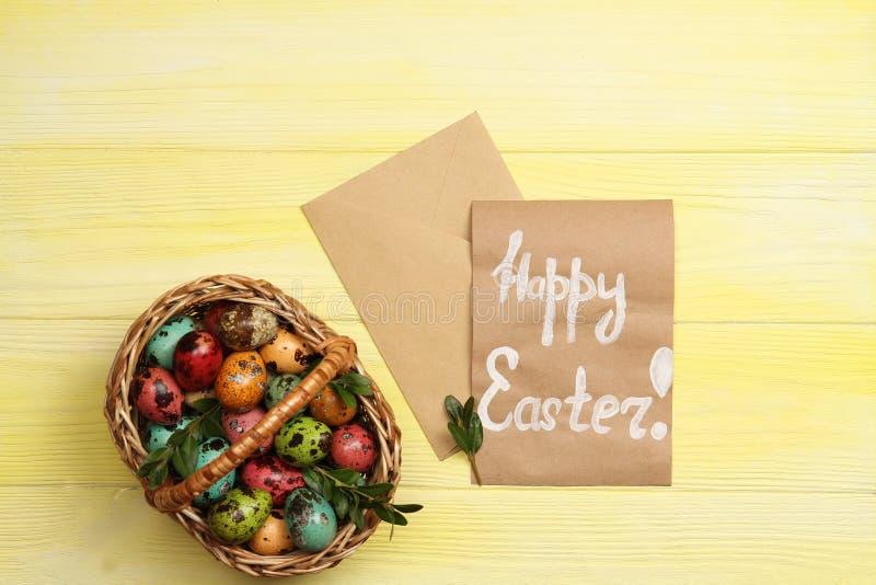 Wielkanocni jajka w koszu z szczęśliwym Wielkanocnym kartka z pozdrowieniami fotografia stock