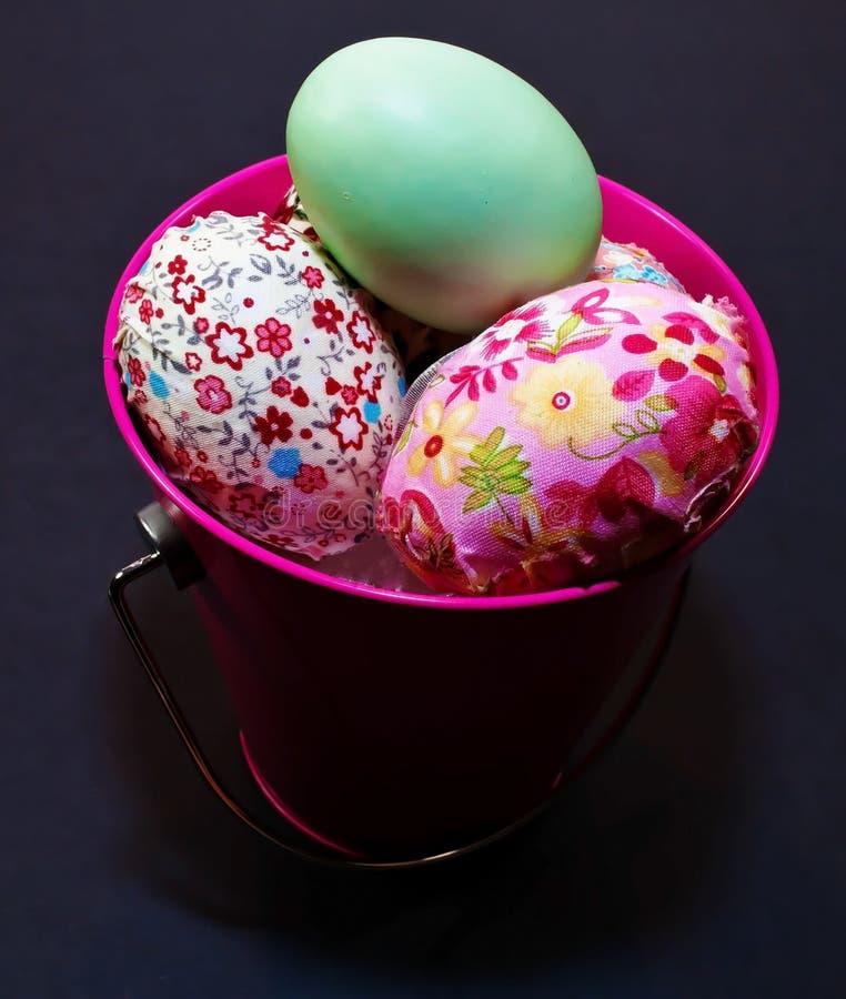 Wielkanocni jajka w różowym wiadrze z jajkami iluminującymi zdjęcia royalty free