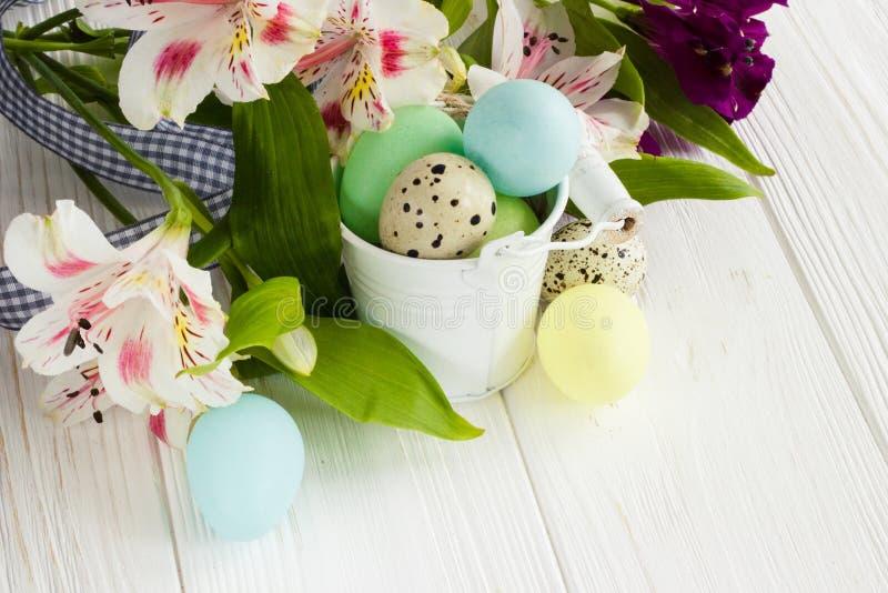 Wielkanocni jajka w wiadrze na białym drewnianym stole z pięknym f obrazy stock