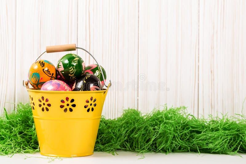 Wielkanocni jajka w wiadrze na drewnianym tle z zieloną trawą zdjęcia royalty free