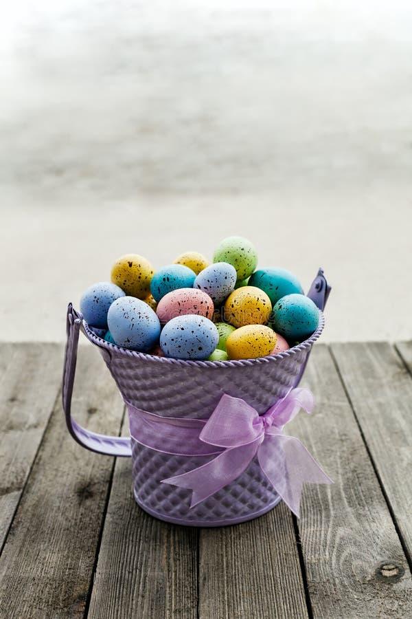 Wielkanocni jajka zbierający w purpurowym wiadrze z faborkiem wokoło zdjęcia stock