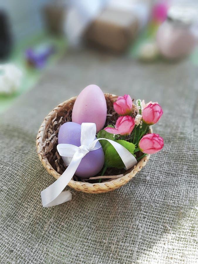 Wielkanocni kolorowi jajka i wiosna kwiaty w koszu na burlap tle zdjęcia royalty free