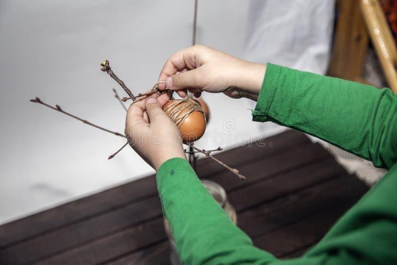Wielkanocni wakacyjni przygotowania Chłopiec wiesza Easter jajka Śliczny dzieciak dekoruje jajka zdjęcie stock