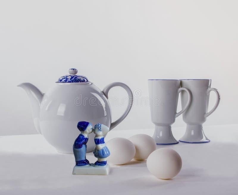 Wielkanocny śniadaniowy Biały herbata set, Easter jajka i tradycyjna Holenderska pamiątkarska symboliczna postać buziak na bielu, zdjęcia stock