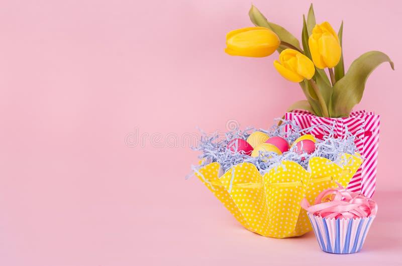 Wielkanocny świąteczny tło - kolor żółty, błękit, czerwoni jajka w żółtym koszu, tulipany, babeczka na pastelowych menchii tle z  fotografia stock